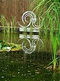 metal outdoor sculpture by garden pond