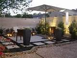 stylish patio garden designed with stones and large containers having ...