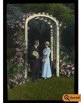 Couple under flower- covered white garden arch, undated