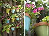 paint the pots in different colors and hang them on the fence