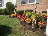 Beautiful fall flowers and scare crows by manicured shrubs atop a bed ...