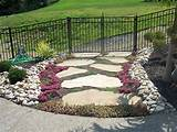 pretty landscaped area with flowers and alternating rows of pebbles