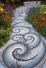 Stone walkway in the garden leading to a garden bench, with twists and ...