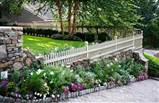 charming wood fence along stone wall flower beds and green grass