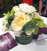 Low centerpiece of green cymbidium orchids, ivory garden roses, spray ...