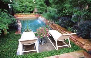 ... pool or spool surrounded by lush landscaping in an urban backyard