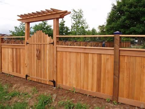 This cool looking wood gate has a small pergola on top.