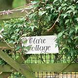 Five bar country gate with trailing ivy and painted house name