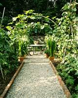 garden a gravel pathway leading to a table and chairs in a garden ...