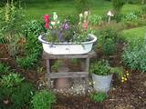 simple old enamel pan on a wooden stand is centered in the garden bed