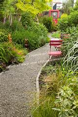 gravel garden path leads between lush beds, past red painted metal ...
