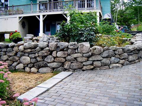 border of rocks forms a rustic looking wall around the home
