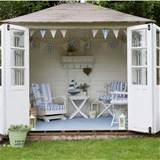 White painted garden room with blue and white chairs, table and ...