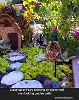 fairy kneeling in fairy garden overlooking sedum lawn stone path and