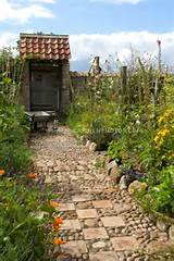 garden path of stones pebbles tiles leading to garden gate door